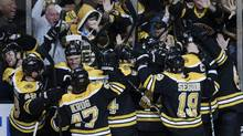Boston Bruins fans and players celebrate after Patrice Bergeron's game-winning goal against the Pittsburgh Penguins during the second overtime period in Game 3 of the NHL hockey Stanley Cup playoffs Eastern Conference finals, in Boston, Thursday, June 6, 2013. (Associated Press)