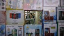 A vendor waits for customers inside his shop selling mobile phones at Surat, in the western Indian state of Gujarat Jan. 4, 2013. (AMIT DAVE/REUTERS)