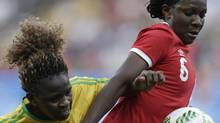 Canada's Deanne Rose, right, and Zimbabwe's Sheila Makoto fight for the ball during a an Olympic soccer match on Aug. 6, 2016. (Nelson Antoine/The Associated Press)