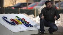 A man gives two thumbs up as he pose for a photo outside the Google China headquarters in Beijing (Ng Han Guan)