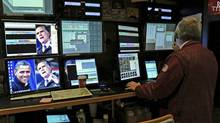 Images of U.S. President Barack Obama, left, and Republican Mitt Romney are seen on a monitor while a trader works on the floor of the New York Stock Exchange in New York the day after the election. (Peter Foley/Bloomberg)