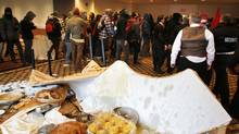 Student protesters leave after overturning a table filled with croissants and orange juice prior to the National Bank Financial Group annual general meeting in Montreal April 4, 2012. (CHRISTINNE MUSCHI/REUTERS/CHRISTINNE MUSCHI/REUTERS)