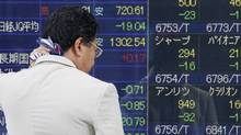 A man wipes sweat from his neck as he looks at an electronic stock board of a securities firm in Tokyo on July 23, 2012.  (Koji Sasahara/AP)