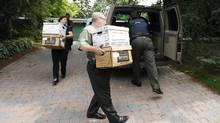 Agents of the Royal Gendarmerie of Canada, carry boxes of documents from the home of Jacques Corriveau, Wednesday July 4, 2007, in Saint-Bruno-de-Montarvile, Que. Now 83 years old, Mr. Corriveau is scheduled to appear in a courtroom in Montreal on Tuesday, three years after the RCMP arrested him on charges of fraud, forgery and laundering proceeds of crime. (Francois Roy/CP)