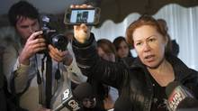 Maret Tsarnaeva, an aunt of the two suspects in the Boston Marathon bombing, holds a reporter's smart phone which displays a scene from the bomb site, as she speaks to journalists in the lobby of her apartment building in Etobicoke, Ontario, on Friday April 19, 2013. (Chris Young/The Canadian Press)