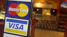 Signs for credit cards are shown at the entrance to a New York coffee shop. (MARK LENNIHAN/ASSOCIATED PRESS)