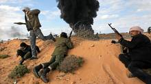 Libyan rebels under fire from pro-Gadhafi forces take cover near a burning gas facility close to Ras Lanuf, Libya, on Wednesday. (John Moore/Getty Images)