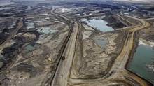 Giant dump trucks haul raw oil sands to be processed at the Suncor mining operations near Fort McMurray, Alta., earlier this year. (TODD KOROL/REUTERS)