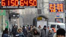 Pedestrians in Moscow walk under a board listing foreign currency rates against the ruble on Monday. (VASILY MAXIMOV/AFP/Getty Images)