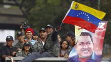 Supporters of Venezuela's President Hugo Chavez ride on the top of a truck in front of a military hospital, where Chavez is being treated, in Caracas February 19, 2013. (Carlos Garcia Rawlins/REUTERS)