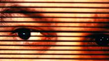 Man's eyes, view through open blinds, close-up____Do Not Archive (Jed Share/Getty Images)