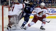 Phoenix Coyotes' goaltender Mike Smith gives Winnipeg Jets' Dustin Byfuglien a shot to the face during second period NHL hockey action in Winnipeg, Monday, January 13, 2014. (Trevor Hagan/THE CANADIAN PRESS)