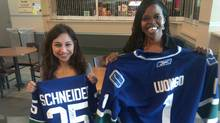 Dallas-based Canucks fans Vanessa Guadiana, left, and Njeri Sims display autographs from their hockey heroes. (David Ebner/The Globe and Mail)