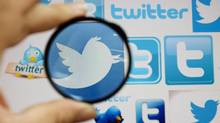 A person holds a magnifying glass over a computer screen displaying Twitter logos (OGNEN TEOFILOVSKI/REUTERS)