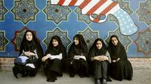 "Iranian women sit under a painting of a revolver during a protest in front of the former U.S. embassy in Tehran to mark the anniversary of Student's Day November 4, 2006. Thousands of Iranians on Saturday chanted ""Death to America"" outside the former U.S. embassy which students stormed on this day in 1979, renewing Iran's defiance at a time when it faces possible sanctions for its nuclear work. (MORTEZA NIKOUBAZL/REUTERS)"