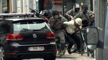 In this framegrab taken from VTM, armed police officers escort Salah Abdeslam to a police vehicle during a raid in the Molenbeek neighborhood of Brussels, Belgium, Friday March 18, 2016. The identity of Salah Abdeslam is confirmed Saturday March 19, 2016, by French police and deputy mayor of Molenbeek, Ahmed El Khannouss quoting official Belgium police sources. After an intense four-month manhunt across Europe and beyond, police on Friday captured Salah Abdeslam, the top suspect in last year's deadly Paris attacks, in the same Brussels neighborhood where he grew up. (VTM via AP) BELGIUM OUT)