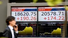 A pedestrian walks past an electronics stocks indicator by the window of a securities company, displaying the closing rate of Tokyo Stock Exchange, in Tokyo on April 21, 2017. The benchmark Nikkei 225 rose 1.03 per cent, or 190.26 points, to close at 18,620.75. (TOSHIFUMI KITAMURA/AFP/Getty Images)