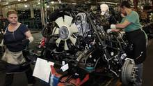 Two General Motors auto assembly workers assemble engines for the Chevrolet Silverado and GMC Sierra pickup trucks at the Flint Assembly in Flint, Mich., in this file image from 2011. (REBECCA COOK/Reuters)