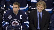 Winnipeg Jets left wing Andrew Ladd (left) and Jets part-owner David Thomson smile as they pose with the rest of the Jets during a team photo prior to a practice in Winnipeg, Saturday, Oct. 8, 2011. The Jets will play the Montreal Canadiens in their inaugural game on Sunday. (JONATHAN HAYWARD/THE CANADIAN PRESS)
