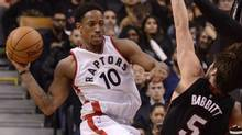 DeMar DeRozan passes into the key while being defended by Luke Babbitt on Friday. (Jon Blacker/THE CANADIAN PRESS)