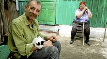Pripyat-Mikhail Shpak (left) holds a cat he is fond of, while his mother, Tamara Vorobey, sits in the background. (Nic Hume/Nic Hume)