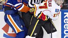 Calgary Flames Blake Comeau (17) checks Edmonton Oilers Magnus Paajarvi (91) into linesman David Brisbois during second period NHL action in Edmonton, Alta., on Monday April 1, 2013. (JASON FRANSON/THE CANADIAN PRESS)