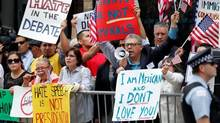 In this June 29, 2015, file photo, protesters gather across the street from a restaurant in Chicago before Republican presidential candidate Donald Trump spoke to members of the City Club of Chicago. (AP Photo/Charles Rex Arbogast, File)