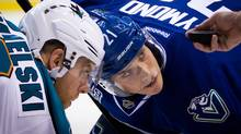 Vancouver Canucks' Mason Raymond right, and San Jose Sharks' Joe Pavelski wait for linesman Ryan Galloway to drop the puck as they face off during the first period of an NHL hockey game in Vancouver, B.C., on Tuesday March 5, 2013. (The Canadian Press)