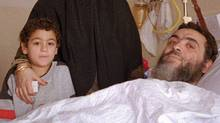 Ahmed Said Khadr,, a suspect in the suicide bombing of the Egyptian Embassy in Islamabad, is visited by his wife and one of his sons on Jan. 1, 1996, at a hospital in Islamabad. (AP)