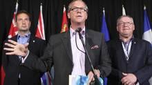 Saskatchewan Premier Brad Wall, middle, is shown with PEI Premier Robert Ghiz at left in July, 2012. (ADAM SCOTTI/REUTERS)