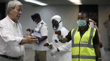 Nigerian port health officials uses a thermometer on a worker at the arrivals hall of Murtala Muhammed International Airport in Lagos, Nigeria, Wednesday, Aug. 6, 2014. A Nigerian nurse who treated a man with Ebola is now dead and five others are sick with one of the world's most virulent diseases, authorities said Wednesday as the death toll rose to at least 932 people in four West African countries. (Sunday Alamba/AP)