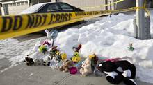 Flowers and stuffed animals lay on the sidewalk as police continue to investigate the scene where multiple shooting deaths occurred in a north Edmonton home, in Edmonton, Alta., on Wednesday, December 31, 2014. (Jason Franson/The Canadian Press)