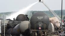 Firefighters apply water to railway cars a day after a Montreal, Maine and Atlanic train derailed, causing explosions of railway cars carrying crude oil in Lac-Mégantic, Que., on July 7, 2013. (Paul Chiasson/The Canadian Press)