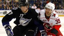 Tampa Bay Lightning's Victor Hedman, left, of Sweden, and Carolina Hurricanes' Patrick Dwyer battle for the puck during the first period of an NHL hockey game on Friday, March 25, 2011, in Tampa, Fla. The Hurricanes won 4-3. (Mike Carlson/Associated Press)