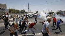 Palestinian protesters run away from tear gas fired by Israeli soldiers during clashes after Friday prayers in the Arab east Jerusalem neighbourhood of Ras al-Amud July 4, 2014. (AMMAR AWAD/REUTERS)