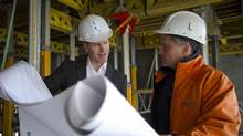Mark Stables of Benchmark, left, and L-Tower site supervisor Eddie Estrela go over plans in the space where the fitness area will be in the condominium tower under construction inToronto. (Kevin Van Paassen/Kevin Van Paassen/The Globe and)
