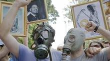 Demonstrators wear gas masks while shouting slogans during a protest against Gabriel Resources, in Bucharest, Romania, in 2011. Gabriel Resources Ltd. says the deadline for a key report needed to debate the fate of its Rosia Montana gold mine in Romania has been extended by three weeks into November, 2013. (Vadim Ghirda/AP)