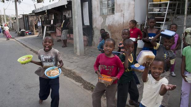 Children head home with their supper from Linda Twala's soup kitchen and community centre, in Johannesburg's Alexandra township.