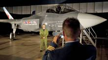 A Canadian Forces pilot has his picture taken in front of a F-35 Joint Strike Fighter prior to a procurement announcement in Ottawa on July 16, 2010. (Adrian Wyld/THE CANADIAN PRESS)