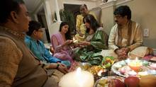 From left, Abhay Dev Shastri leads Mayank and Nikita Thakkar, their grandmother Krishna Luthra, and mother and father Rimple and Satish Thakkar through the Diwali ceremony of prayers and offerings at the Thakkar home in Brampton, Ont. (Tim Fraser/The Globe and Mail)