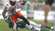 BC Lions slotback Geroy Simon is tackled by Saskatchewan Roughriders cornerback Woodny Turenne during the second half of CFL action in Regina, Sask., Saturday, July 14, 2012. (Liam Richards/THE CANADIAN PRESS)