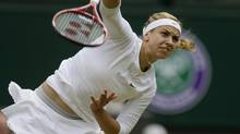 FILE - In this July 1, 2013 file photo, Sabine Lisicki of Germany serves to Serena Williams of the United States in a Women's singles match at the All England Lawn Tennis Championships in Wimbledon, London. (Alastair Grant/AP)