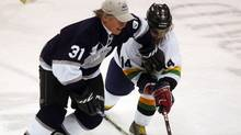 Ex-NHL player Mark Napier (L) fights for the puck against singer Sam Roberts (R) at the Juno Cup hockey game on March 30, 2007 in Prince Albert, Canada. (Jim Ross/2007 Getty Images)