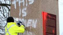 City of Kingston employees remove graffiti on the statue of Sir John A. MacDonald, Canada's first prime minister, in City Park in Kingston, Ont. on Friday Jan. 11, 2013. (Lars Hagberg/THE CANADIAN PRESS)