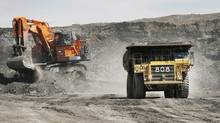 A haul truck carryong a full load drives away from a mining shovel at the Shell Albian Sands oilsands mine near Fort McMurray, Alta., Wednesday, July 9, 2008. (Jeff McIntosh/The Canadian Press/Jeff McIntosh/The Canadian Press)