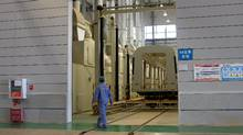 An employee of Chinese state-owned CRRC Corp., a producer of rolling stock, walks past an unfinished metro train car in the company's Kunming factory in Yunnan province. (Reuters Staff/REUTERS)
