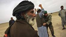 Afghan Army soldiers search civilians for weapons in March, 2007 outside of Lashkar Gah in the Afghan's restive Helmand province. (John Moore/2007 Getty Images)