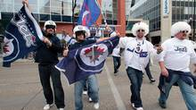 Winnipeg Jets fans celebrate outside the MTS Centre before the Winnipeg Jets game against the Montreal Canadiens before NHL action at the MTS Centre on October 9, 2011 in Winnipeg, Manitoba, Canada. The game is Winnipeg's first NHL regular season game in 15 years. (Photo by Marianne Helm/Getty Images) (Marianne Helm/2011 Getty Images)
