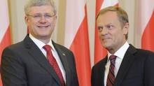 Canada's Prime Minister Stephen Harper, left, and his Polish counterpart Donald Tusk pose for photos before their talks in Warsaw on June 4, 2014. (ALIK KEPLICZ/ASSOCIATED PRESS)