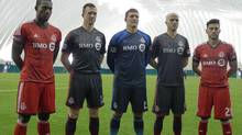 Captain Steven Caldwell (second from left) and Michael Bradley (fourth from left) show off Toronto FC's new onyx alternate uniform in Toronto on Friday, March 7. Joe Bendik (middle) wears the new goalkeeper outfit while Doneil Henry (far left) and Jonathan Osorio (far right) model the team's existing red kit. (NEIL DAVIDSON/THE CANADIAN PRESS)